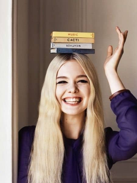 girl with pile of books on head to focused